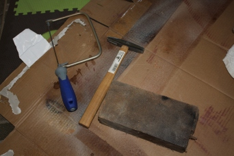 The initial tools: hacksaw, tack hammer, and brick